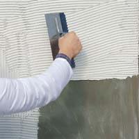 Нанесение клея для мозаики на стену