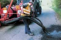 Рис. 11. Заделка выбоин на покрытии прицепной струйно-инъекционной машиной фирмы Bomford (Англия)