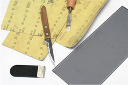 После применения точильного круга по режущей кромке лезвия ножа нужно пройтись наждачной бумагой